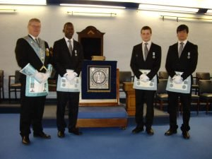 The photograph shows Daniel Orwa, Edward Paul and Maunicio Cadenas proudly wearing their Master Masons apron.